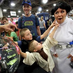 Harper Brace, as Darth Vader, and Collier Brace, as Yoda, try to shock their mother Heather Brace, as Princess Leia, as they attend Comic Con with their father Matt Brace at the Salt Palace Convention Center in Salt Lake City on Saturday, Sept. 7, 2013. The family dressed in Star Wars theme.