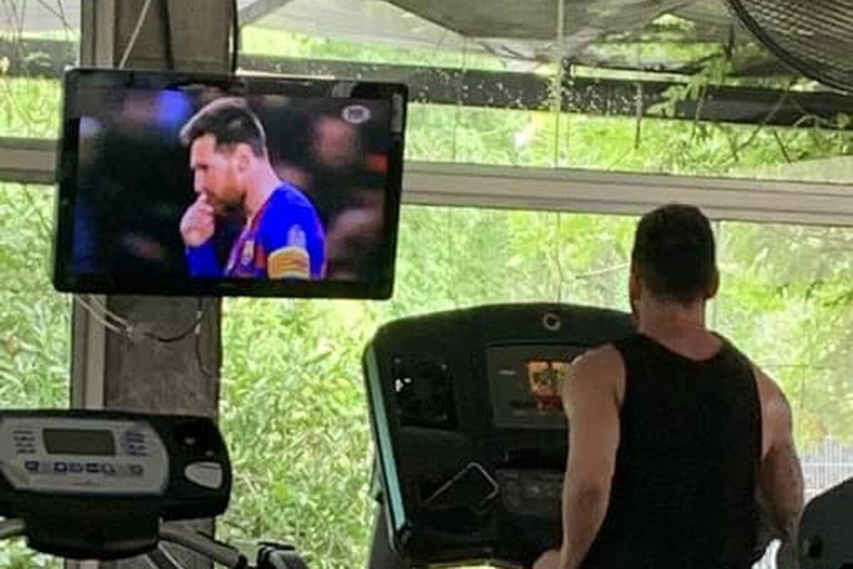 Lionel Messi at the gym while watching his own video on TV