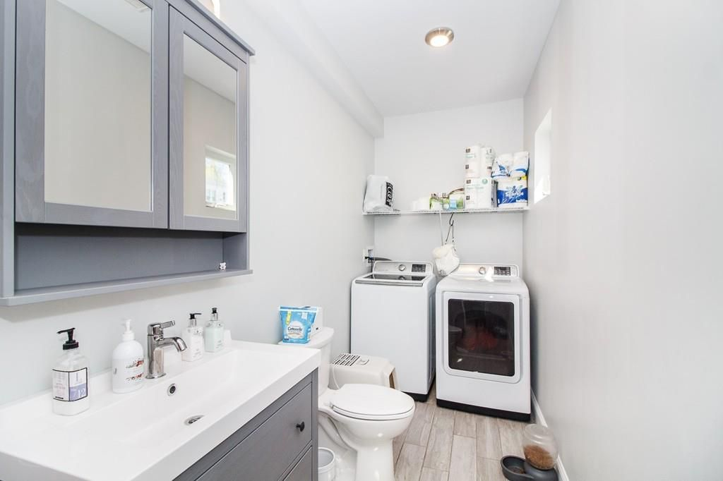 A bathroom with a washer and a dryer side by side at one end.