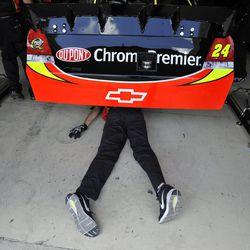 A crew member checks under Jeff Gordon's car during practice for Sunday's NASCAR Sprint Cup Series auto race at Atlanta Motor Speedway, Saturday, Sept. 1, 2012, in Hampton, Ga.