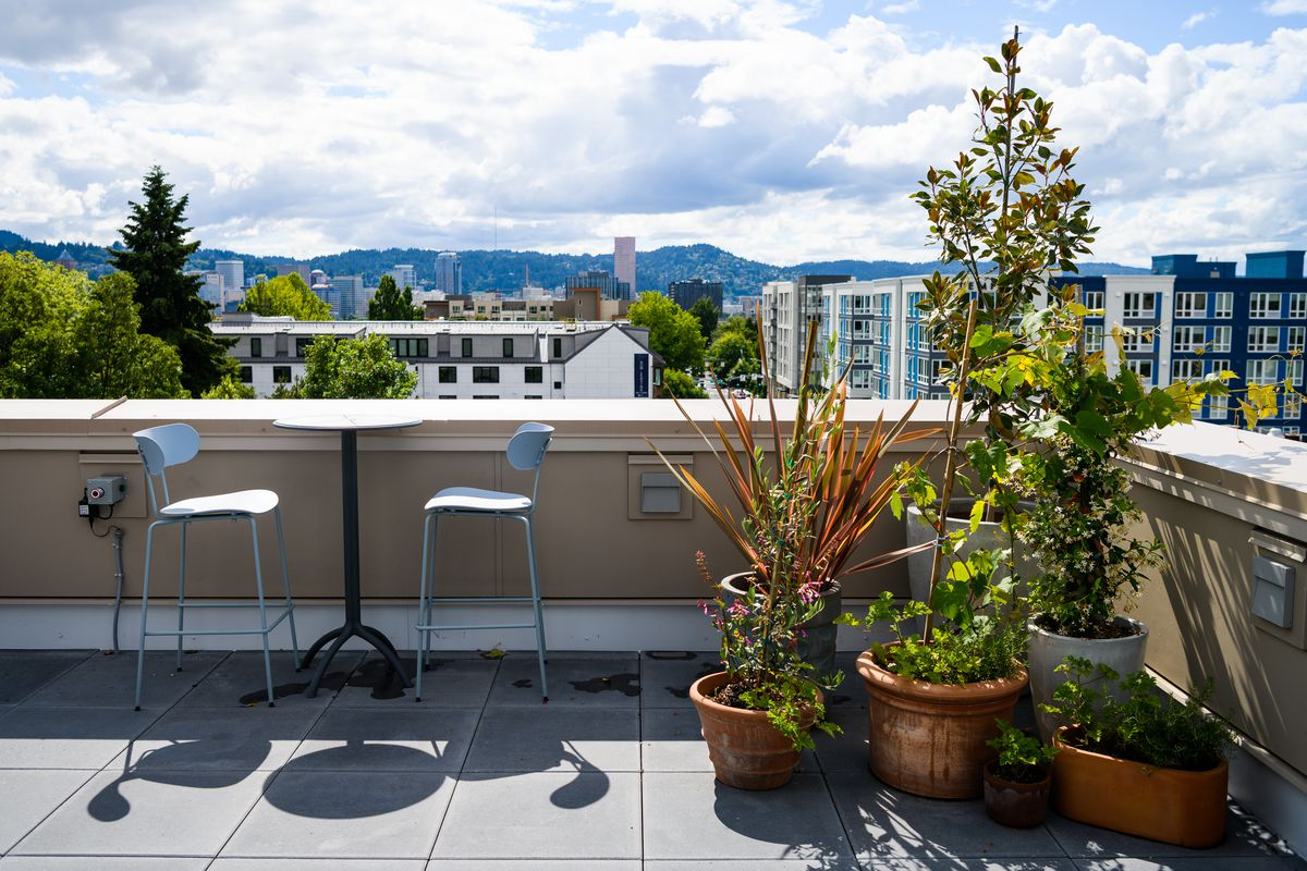 A table with two tall chairs sits next to potted plants on a rooftop with views of Portland's west hills