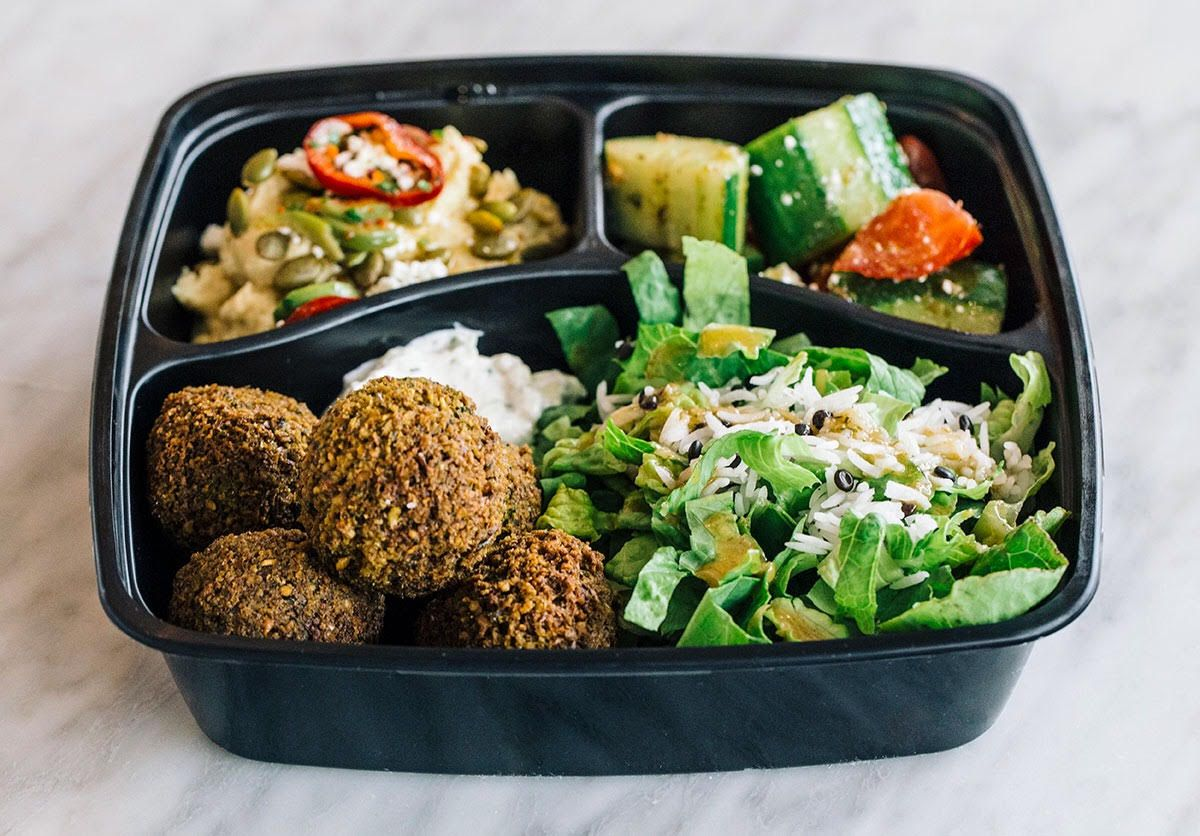 A to-go container filled with falafel and veggies