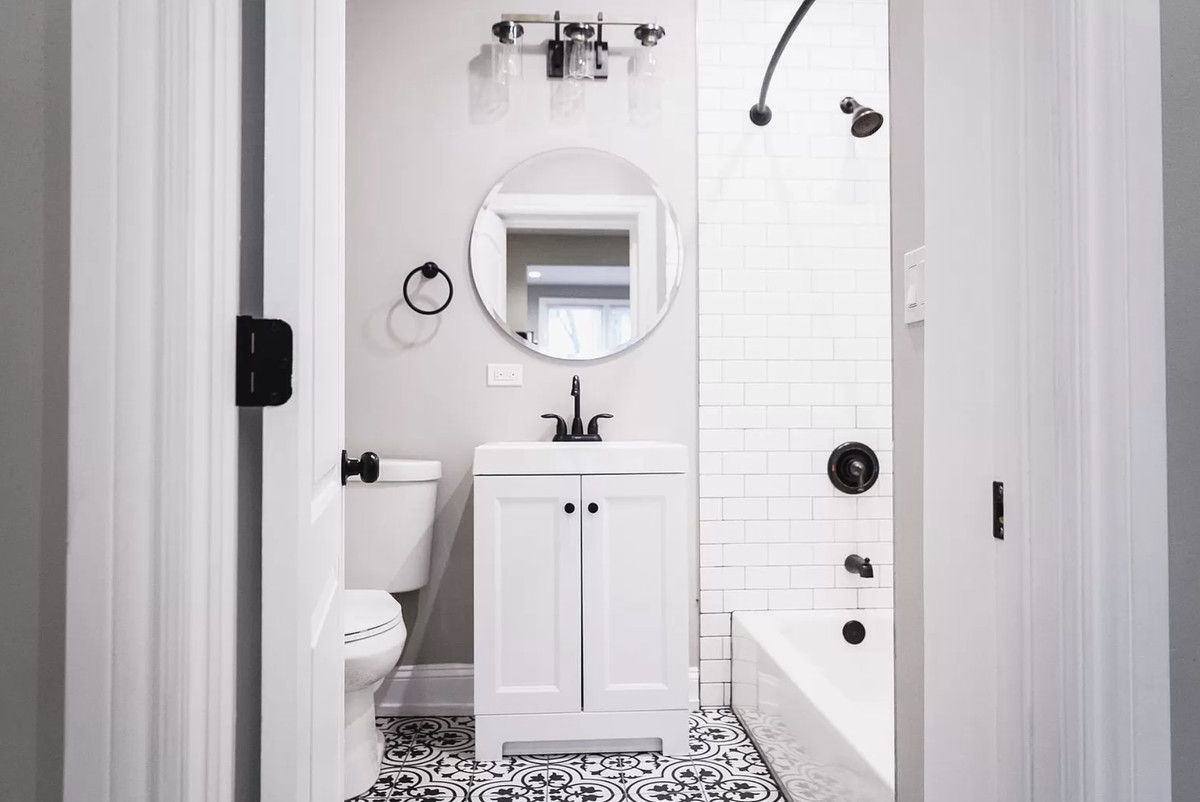 A black and white bathroom with a small cabinet vanity, filigree-patterned tile, and a shower-tub combo.
