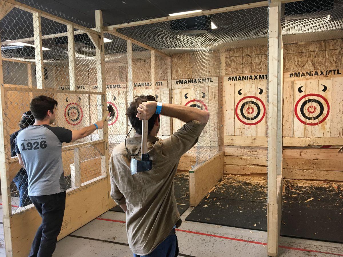 An action shot of Dan Doran and Greg DiLullo throwing axes.