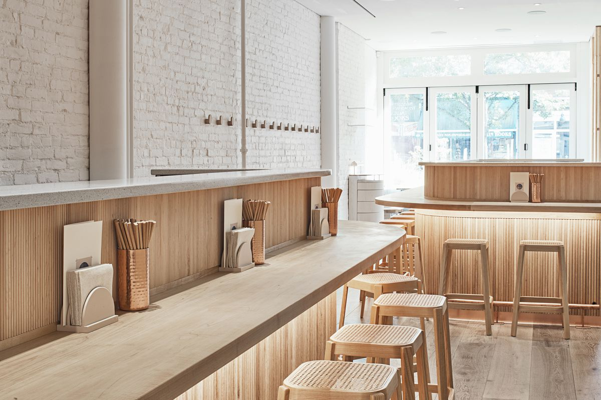 The empty interior of a restaurant with stools lined up against bars for eating