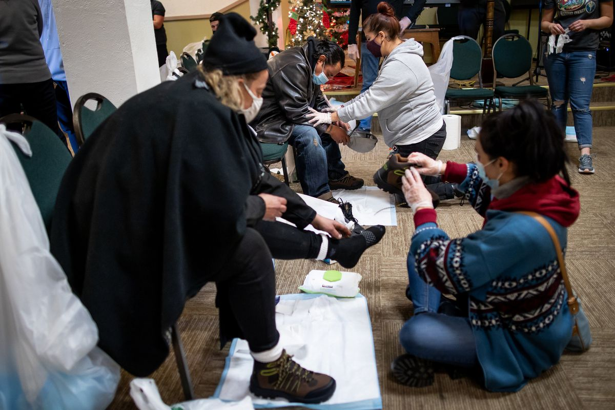 Alexandra Camero, right, outfits Joy Dumas with a pair of boots while Mariela Pedraza, back right, prays with Rene Cuevas, at the Rescue Mission of Salt Lake in Salt Lake City on Saturday, Dec. 19, 2020. Volunteers handed out hundreds of pairs of boots as well as hot meals to people experiencing homelessness.