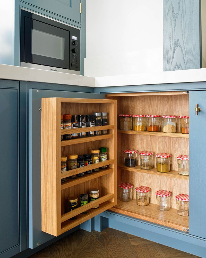 Spices stored inside a blue kitchen cabinet.