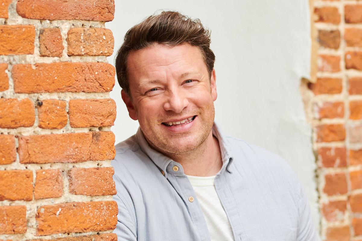Chef Jamie Oliver standing in between two brick walls