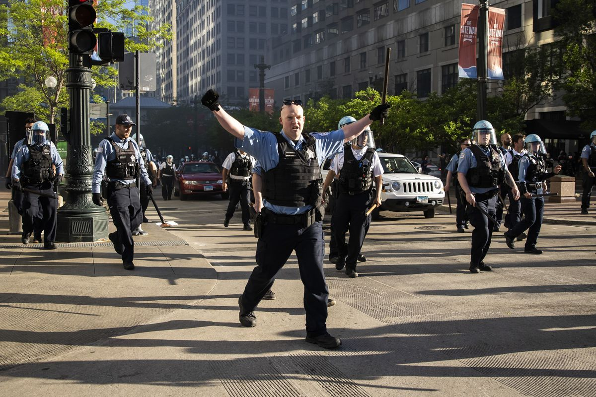 A Chicago police officer reacts to thousands of protesters gathered Saturday on State near Wacker to join national outrage over the killing of George Floyd in Minneapolis police custody.