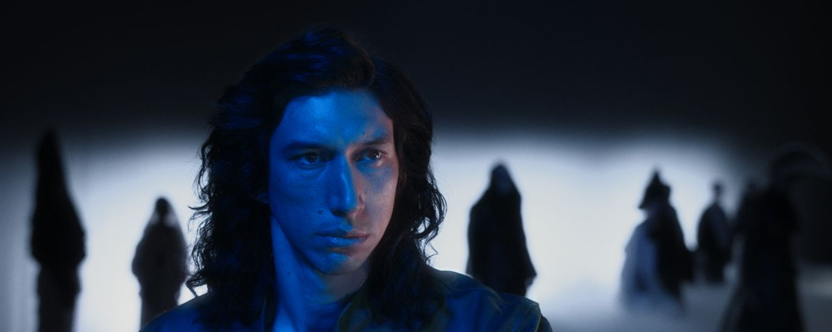 Adam Driver, in dim blue light with fog and tree shapes behind him, in Annette