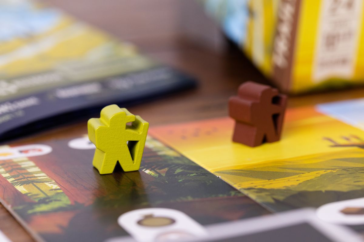 A meeple shaped like a hiker, with a little walking stick and a hat.