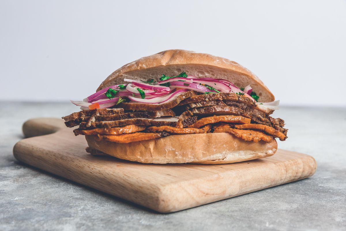 Un sándwich Pan con Chicharron con lomo de cerdo frito, camote a la parrilla y salsa criolla.