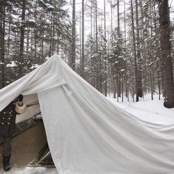 In this Wednesday, April 4, 2012 photo, a female North Korean soldier, working as a guide, opens a protective tent covering the remains of what is said to be a former camp site where the late North Korean leader Kim Il Sung spent the night while leading a battle against the Japanese at the foot of Mount Paektu, North Korea.