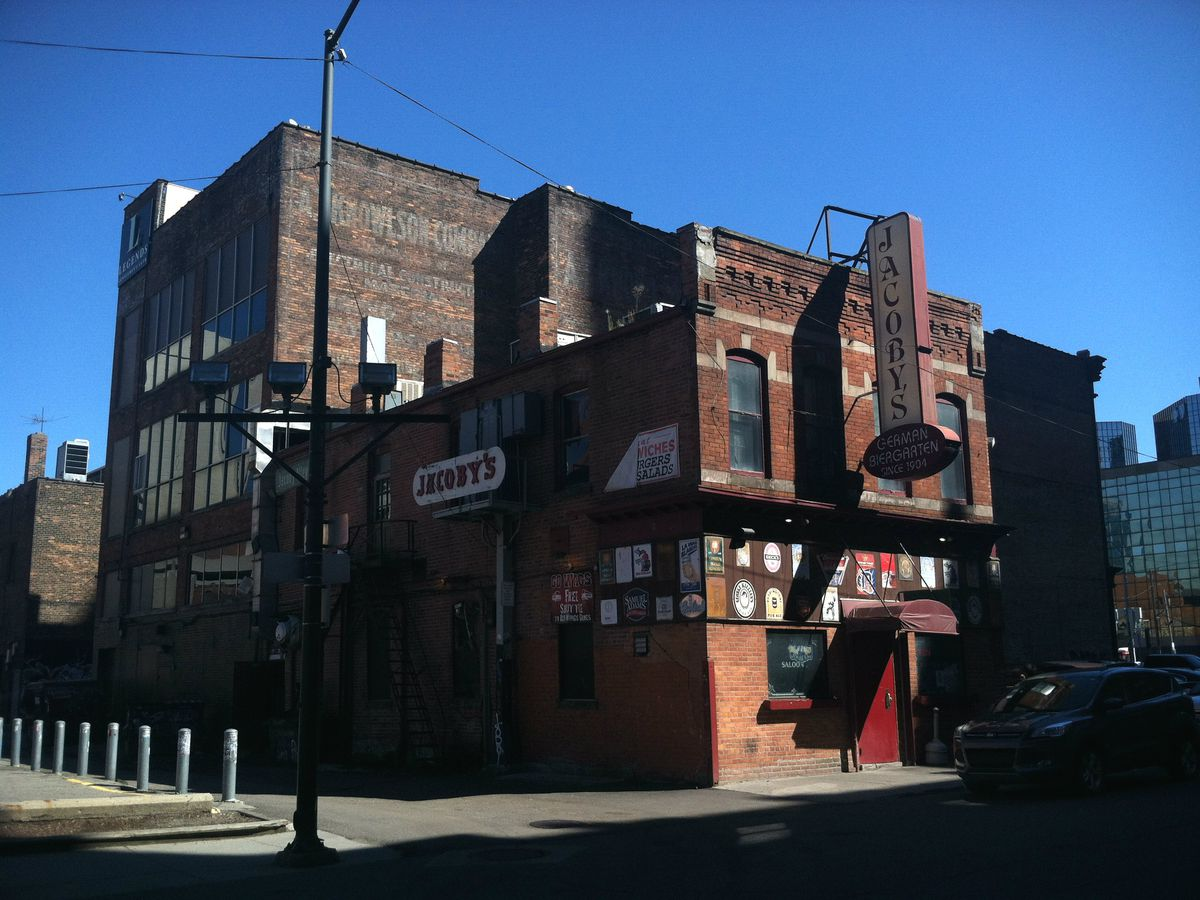 Jacoby's red brick building covered in beer signs is shown on a sunny day with clear blue skies.