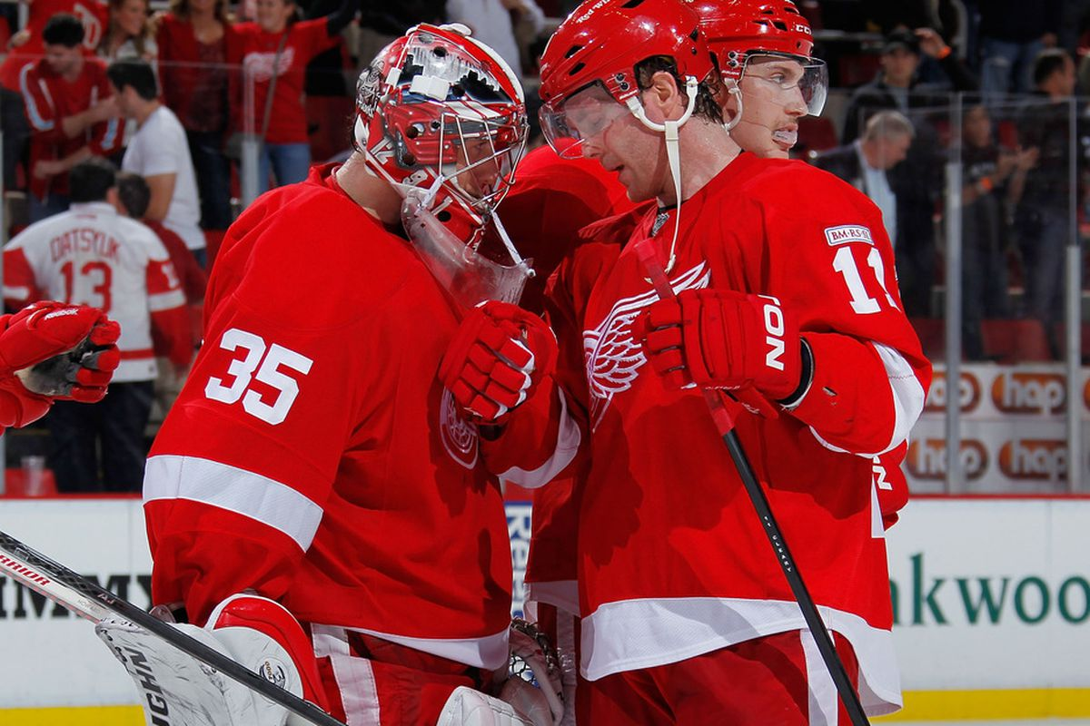 DETROIT, MI - NOVEMBER 08:  Jimmy Howard #35 of the Detroit Red Wings celebrates a 5-2 win over the Colorado Avalanche with Daniel Cleary #11 at Joe Louis Arena on November 8, 2011 in Detroit, Michigan. (Photo by Gregory Shamus/Getty Images)