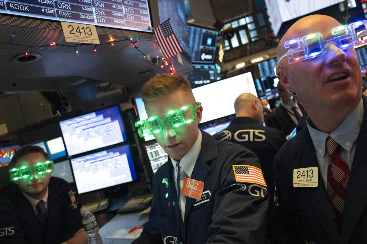 Stock traders wear New Year's 2020 party glasses at the New York Stock Exchange, Tuesday, Dec. 31, 2019.