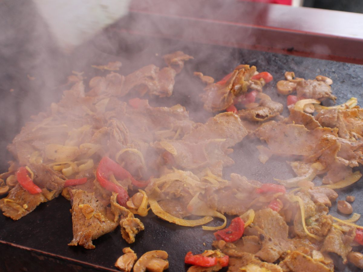 Smoke rises from a flattop grill piled with lamb shawarma and red peppers.