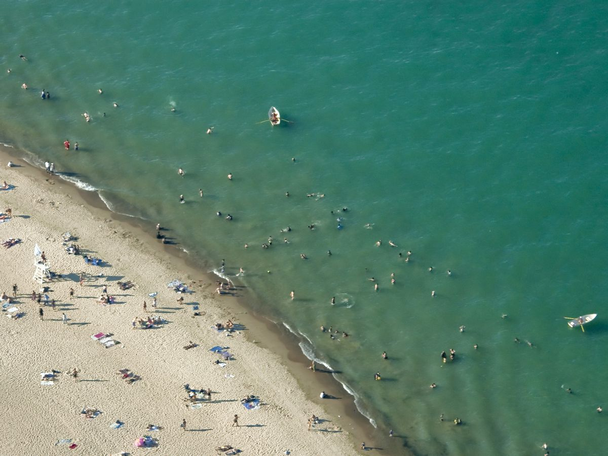 An aerial view of a beach with sand and the ocean. There are beachgoers in both the sand and ocean.