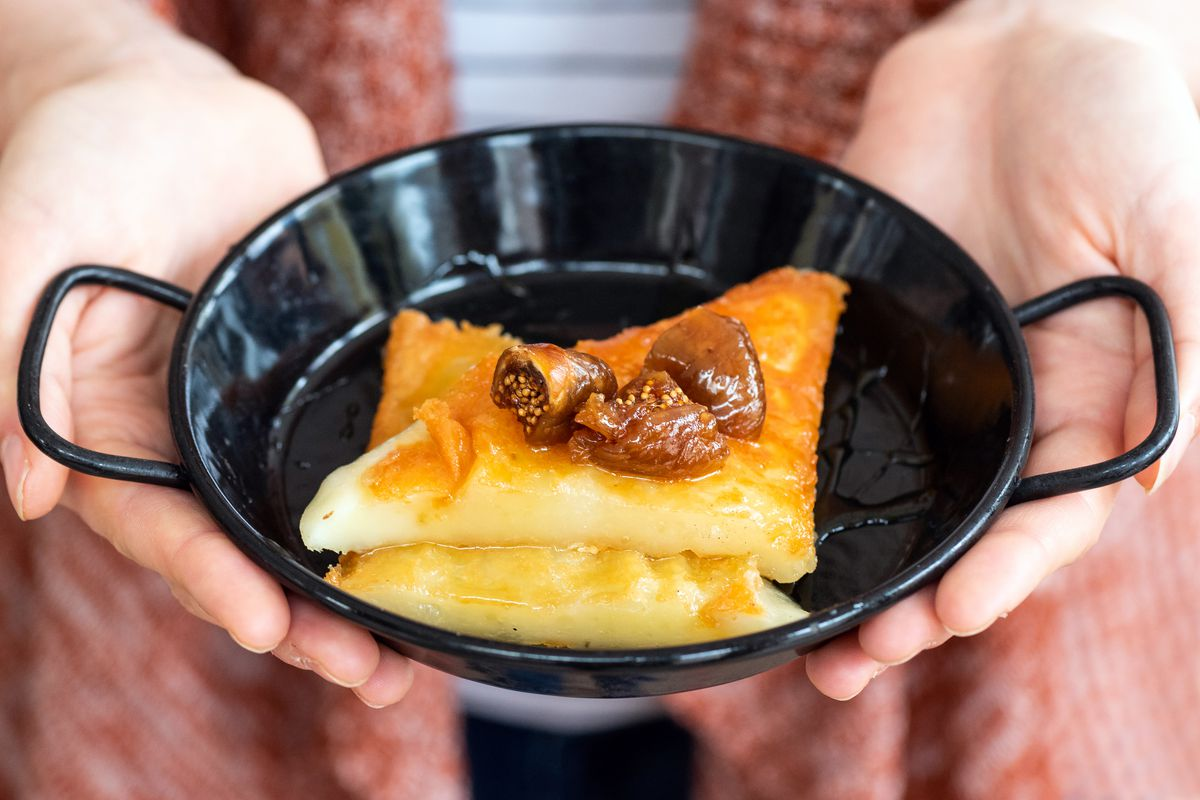 Two hands holding a small cast iron dish with sagnaki topped with figs and honey.