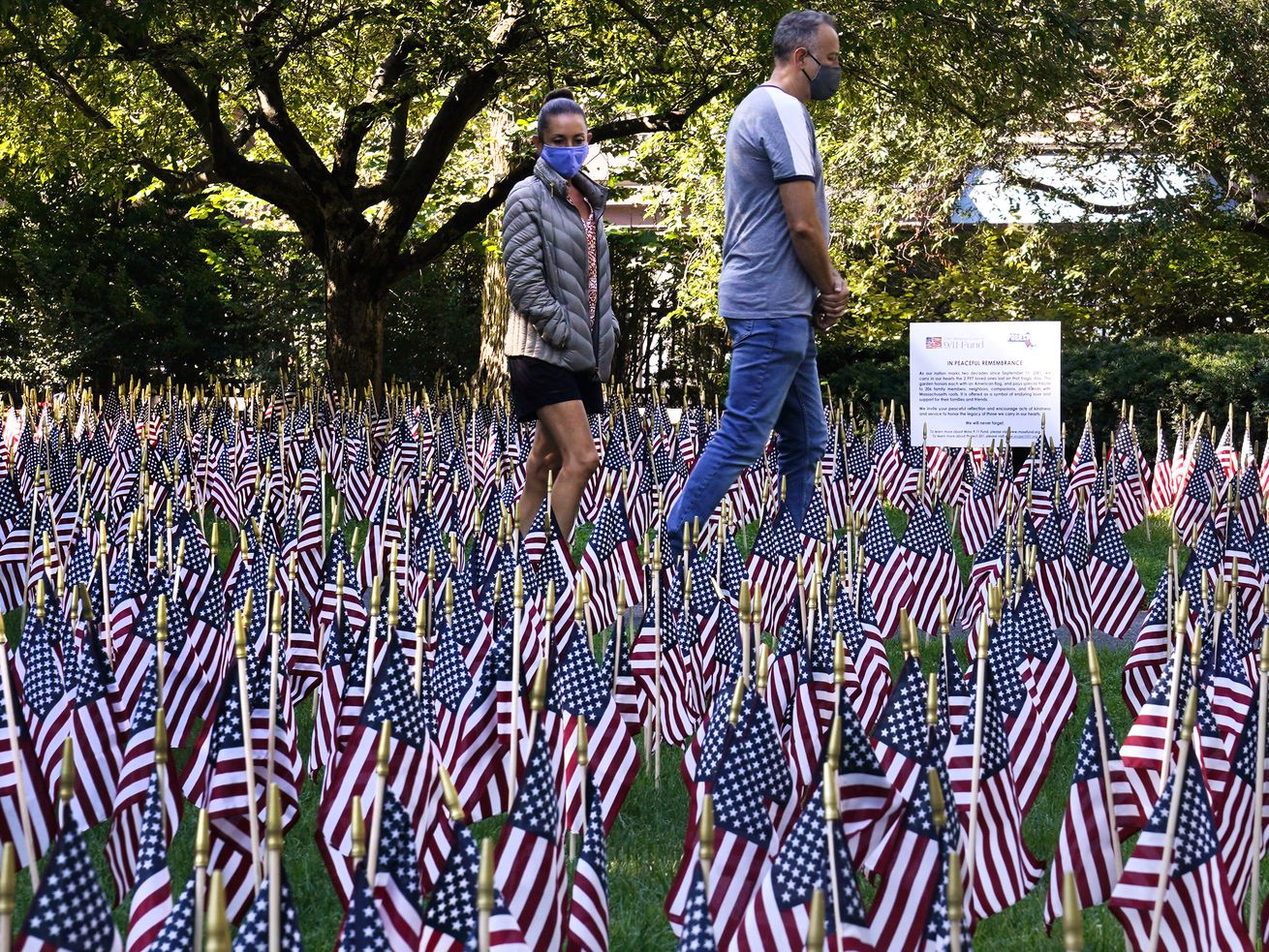 A couple in Boston on Friday walk through a field of almost 3,000 flags, each representing a person who died in the September 11, 2001, attack on the World Trade Center.