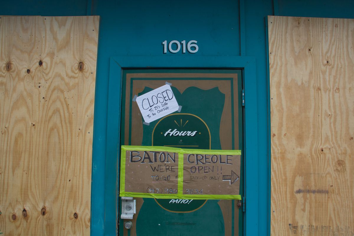 """East Austin bar Shangri-La boarded up its windows and left a sign stating """"Closed Till It's Safe To Be Outside"""" as well as a sign directing people looking for food truck Baton Creole to call or enter through the back for pickup orders"""
