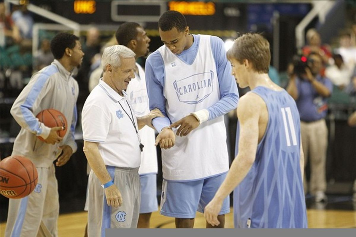 Roy Williams looks at forward John Henson's wrists during practice before  the 2012 NCAA men's basketball tournament at Greensboro Coliseum.