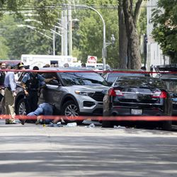 Officers investigate at the scene where a person was shot during a standoff with police Friday morning in the 100 block of South Kilpatrick Avenue.