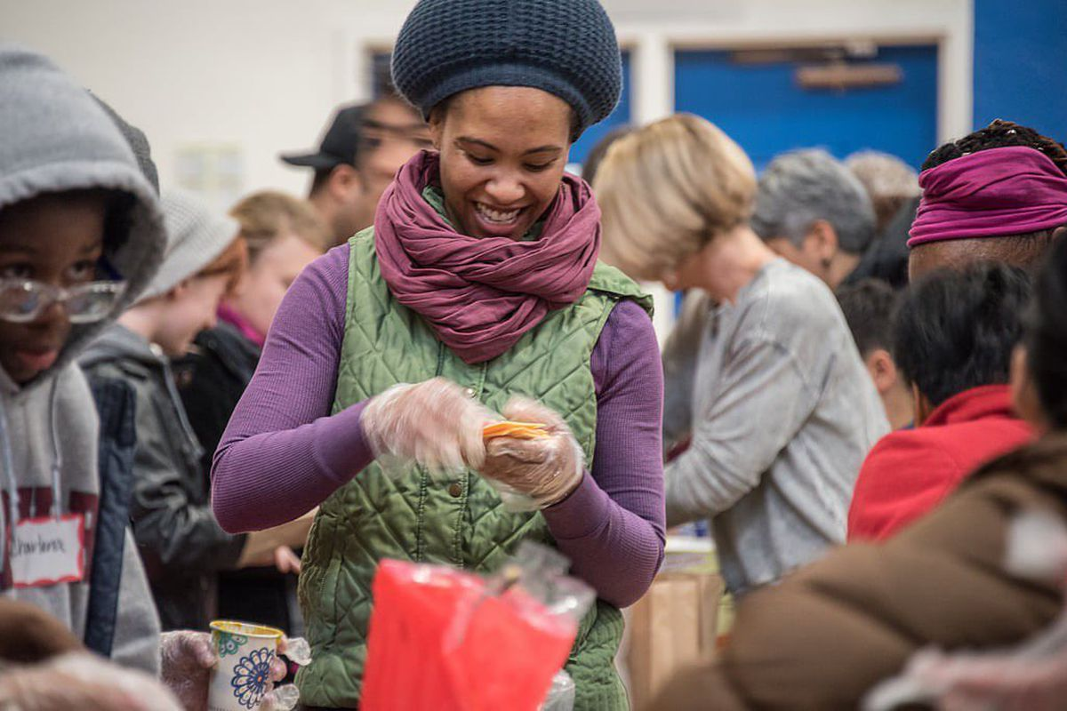 A person in a sweater and hat prepares food in a room full of people.