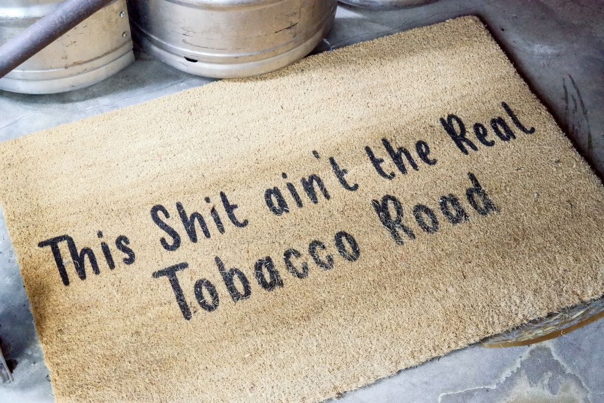 """Tan floor mat that reads """"this shit ain't the real tobacco road"""""""