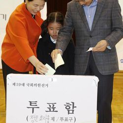 South Korean President Lee Myung-bak, right, and his wife Kim Yoon-ok cast their ballots in the parliamentary elections as their unidentified granddaughter looks on at a polling station in Seoul, South Korea, on Wednesday, April 11, 2012.