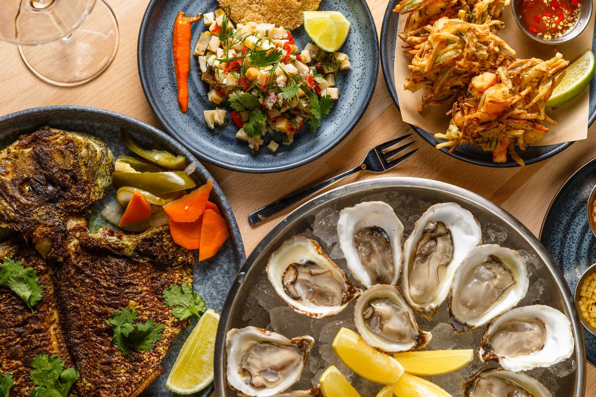 A spread of five plates, including oysters and a flattened fish.