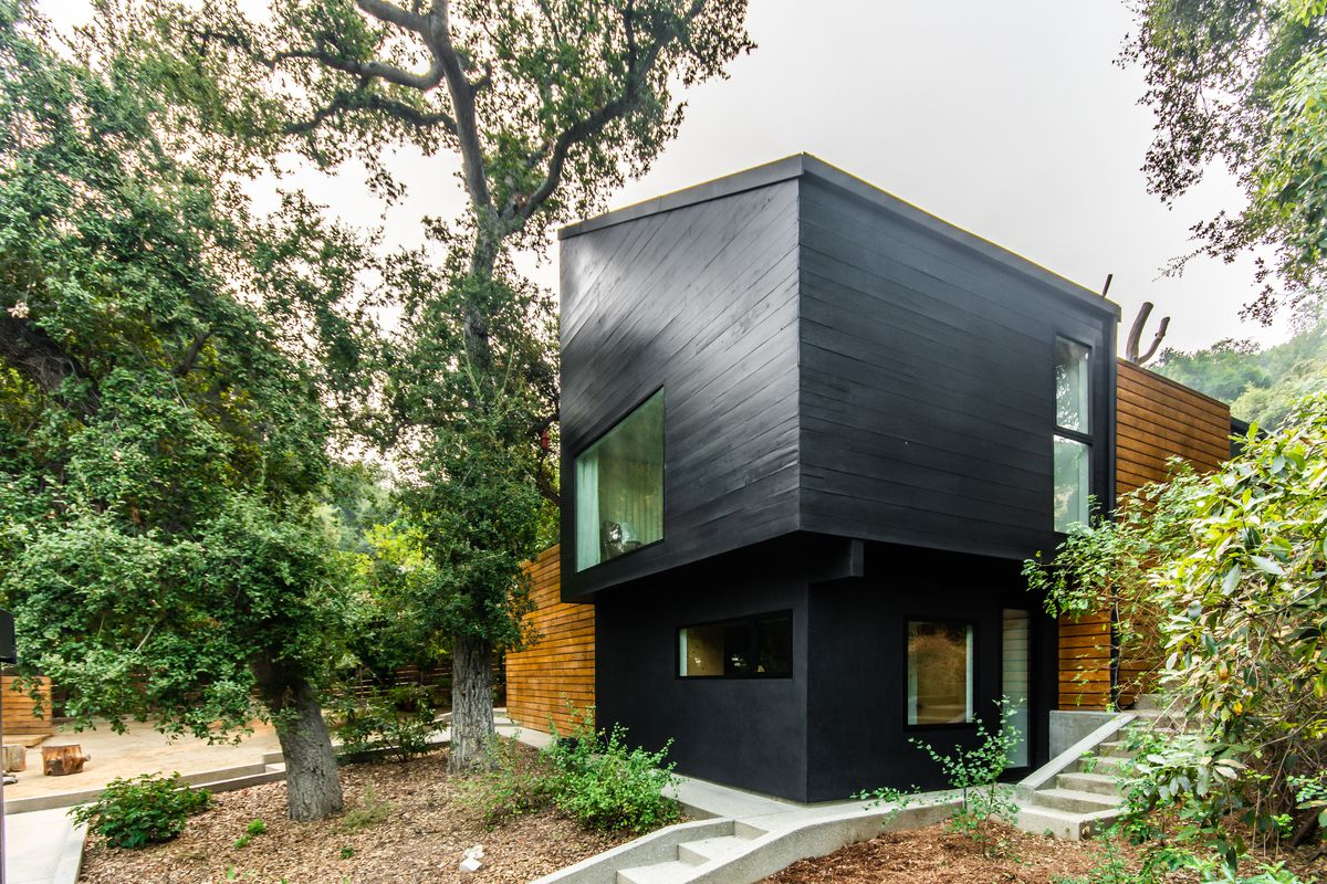 House with black exterior surrounded by trees.