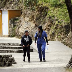 Nurse Lina Rojas, right, walks with a patient at the Fundacion Nina Maria in Alban, Colombia, on Friday, Aug. 23, 2019.
