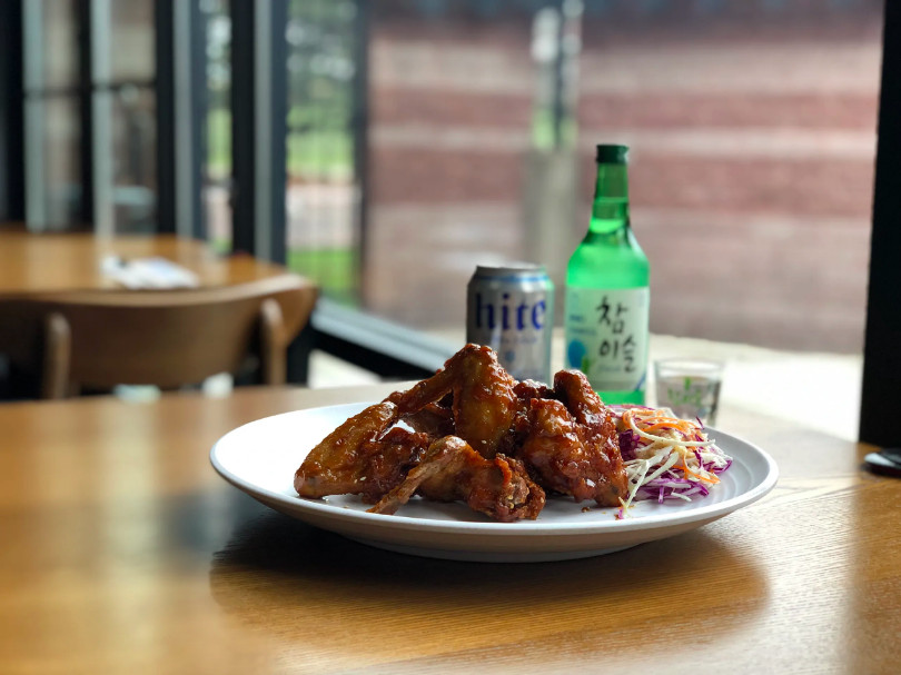A plate of honey glazed Korean fried chicken wings in front of a can of Hite and a green bottle of soju.