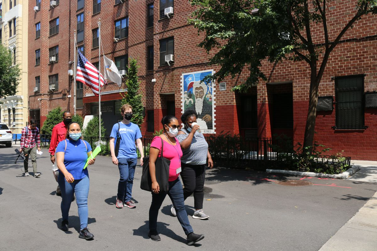 A group of representatives for BronxWorks, each holding informational pamphlets, walk by a large brick building with a small mural on it.