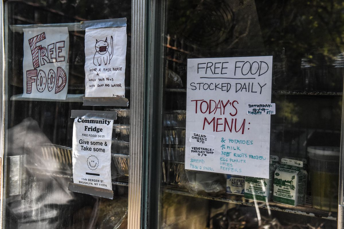 """Signs reading """"free food"""" and """"today's menu"""" are posted to the sliding glass doors of a well-stocked industrial fridge."""