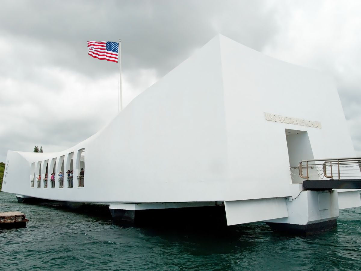 A horizontal, rectilinear white building sits on the water. An American flag flies overhead.