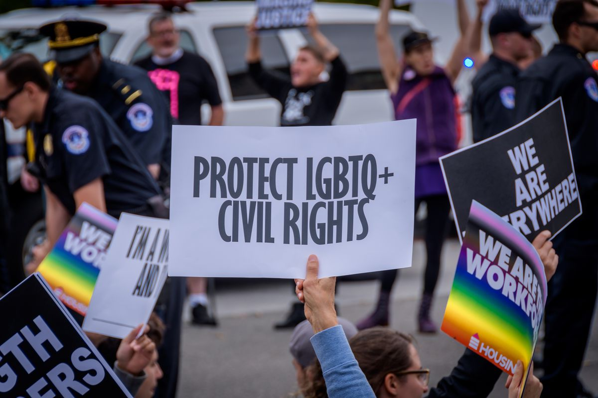 """A demonstrator holds a sign reading, """"Protect LGBTQ+ civil rights."""""""
