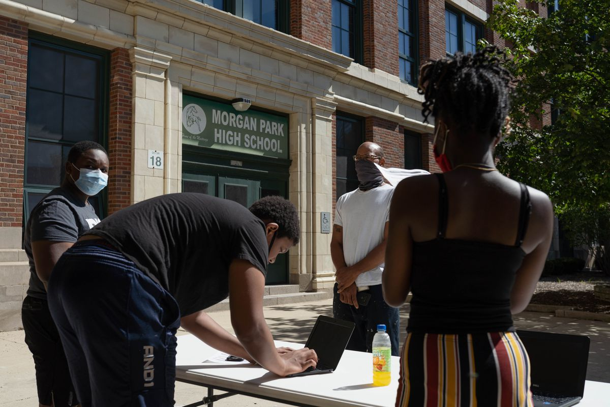 Staff members of Morgan Park High School prepare laptops to be distributed to students at Morgan Park High School in Morgan Park Saturday morning, Sept. 5, 2020. Staff distributed laptops to students before the start of classes.