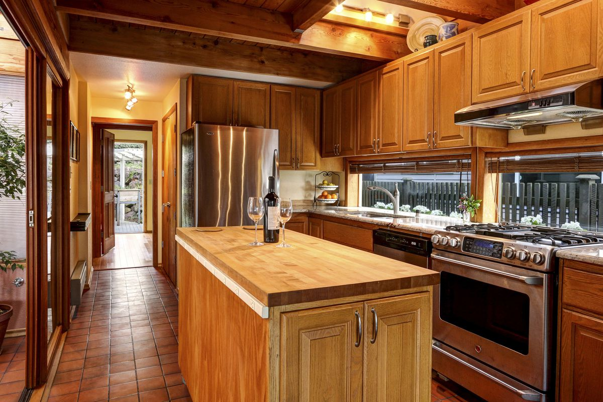 A wood-cabinet kitchen with exposed ceiling beams has a wood-frame, sliding glass door leading to the atrium