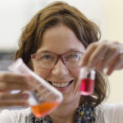 """In this Thursday, Sept. 15, 2011 photo, William & Mary professor Elizabeth Harbron displays vials with merocyanine and rhodamine dye in her lab in Williamsburg, Va. Though she was happy to help blaze a path, Habron says she didn't start out to create an all-women's lab. It happened naturally, with students seeking her out because they liked her informal, lively teaching style. With two-thirds of all undergraduate degrees and 60 percent of master's degrees now going to women, many believe it's only a matter of time before that trend influences the upper echelons of the """"STEM"""" fields - science, technology, engineering and math."""