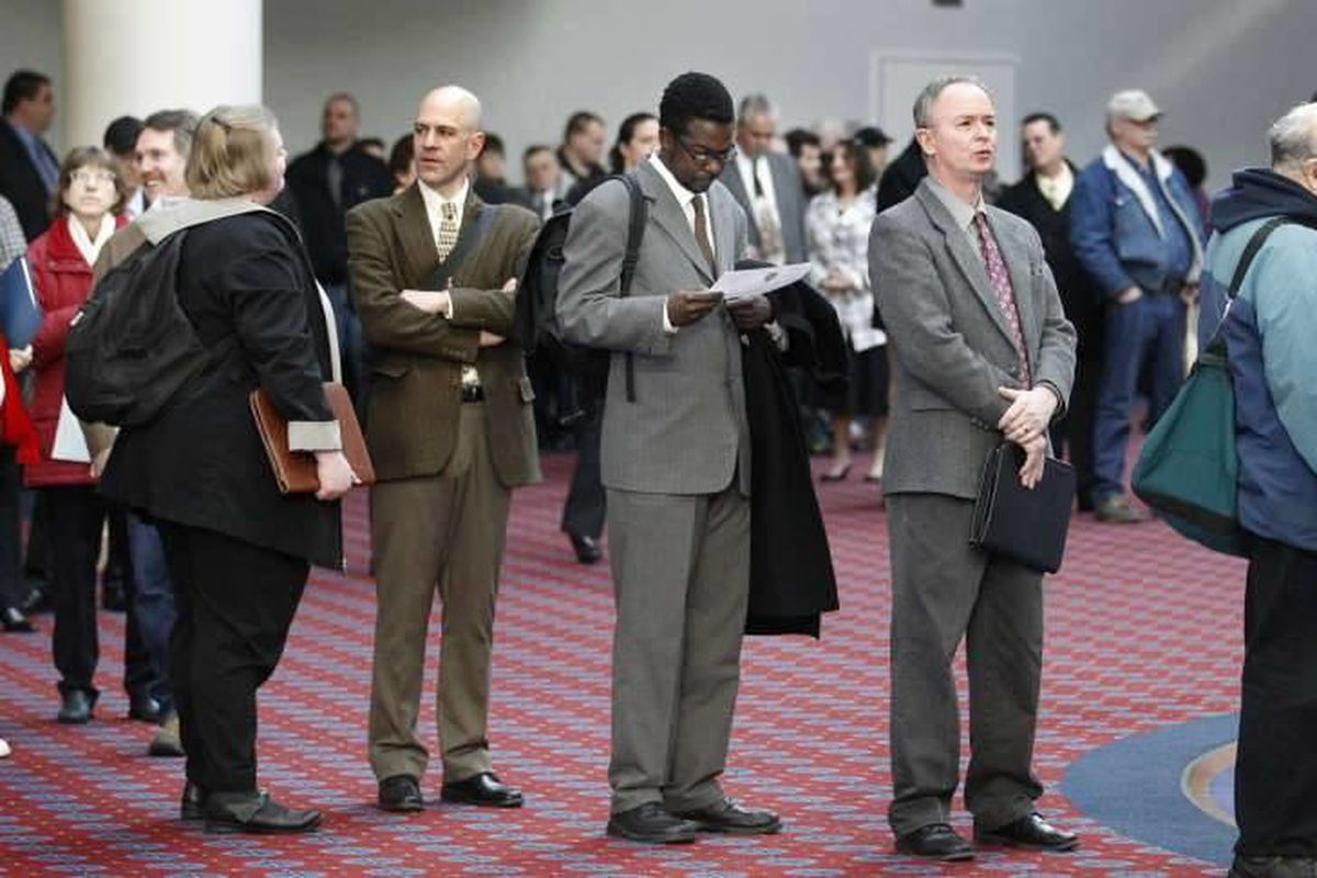 This March 7, 2012, file photo shows job seekers standing in line during the Career Expo job fair in Portland, Ore.