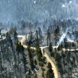 FILE - In this March 27, 2012 photo, one home stands untouched at left while another home at right smolders after burning in the Lower North Fork Wildfire in the foothills community of Conifer, Colo., southwest of Denver. Emergency officials told confused residents not to worry after they reported a fire on the outskirts of Denver, including at least two residents who later were found dead in their burning home, 911 calls released by officials Tuesday showed.