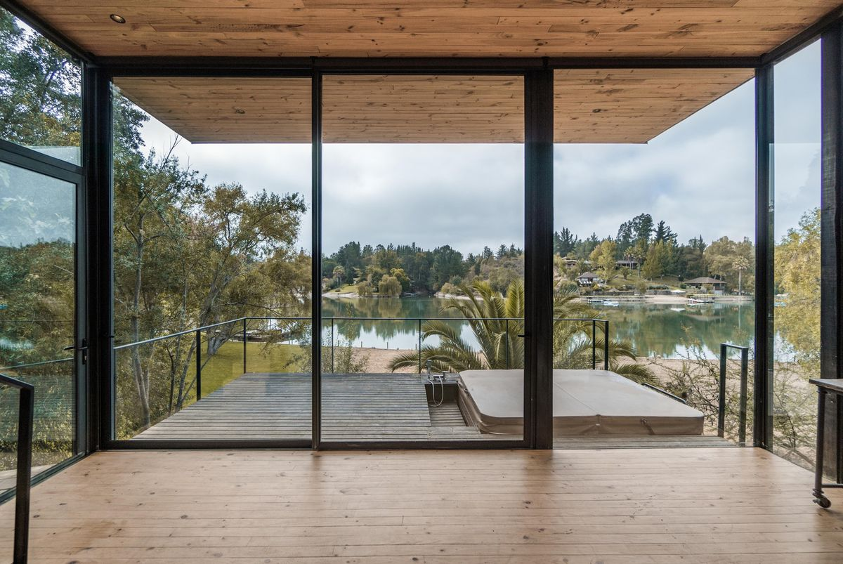 Windows with a lake view open out onto a timber deck with a hot tub.