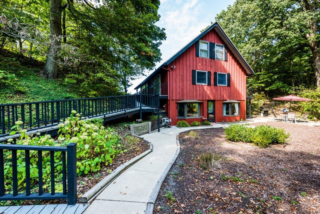 A red cabin with a barn-like aesthetic, four rectangular windows, and two bay windows faces an open yard with a small paved sidewalk and ramp that follows the edge of the woods.