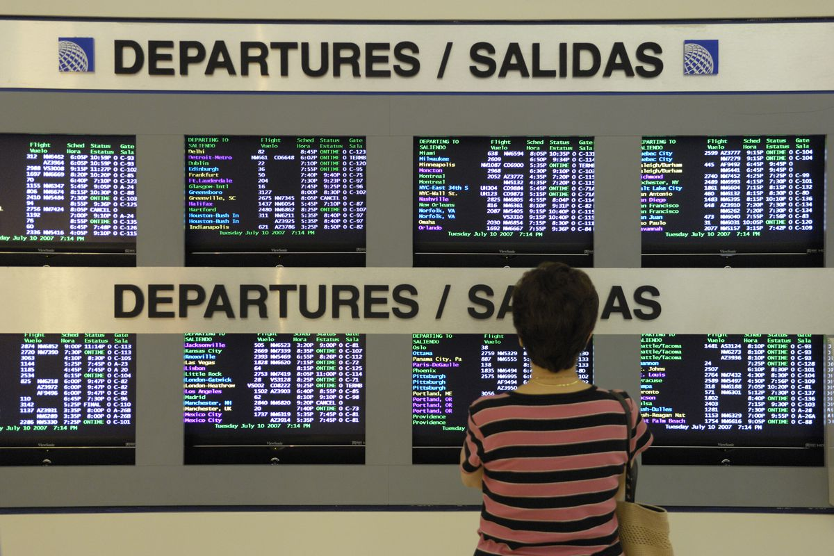a woman passenger looking at the flight departures information screens with signs in the English and Spanish languages in the TerminalC