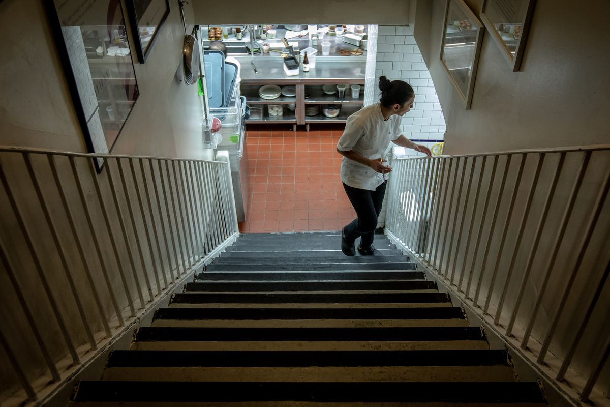 Executive chef Victoria Blamey, wearing a white chef's shirt, stands at the bottom of a staircase, looking out.