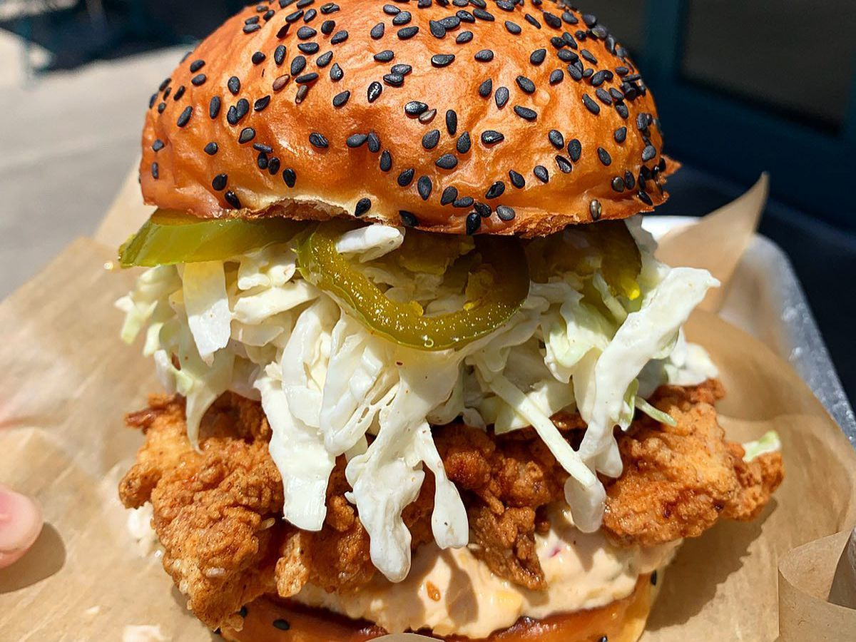"""Crispy fried chicken breast with buttermilk garlic slaw, candied jalapeños, spicy """"pimento"""" cheese on a house made bun"""