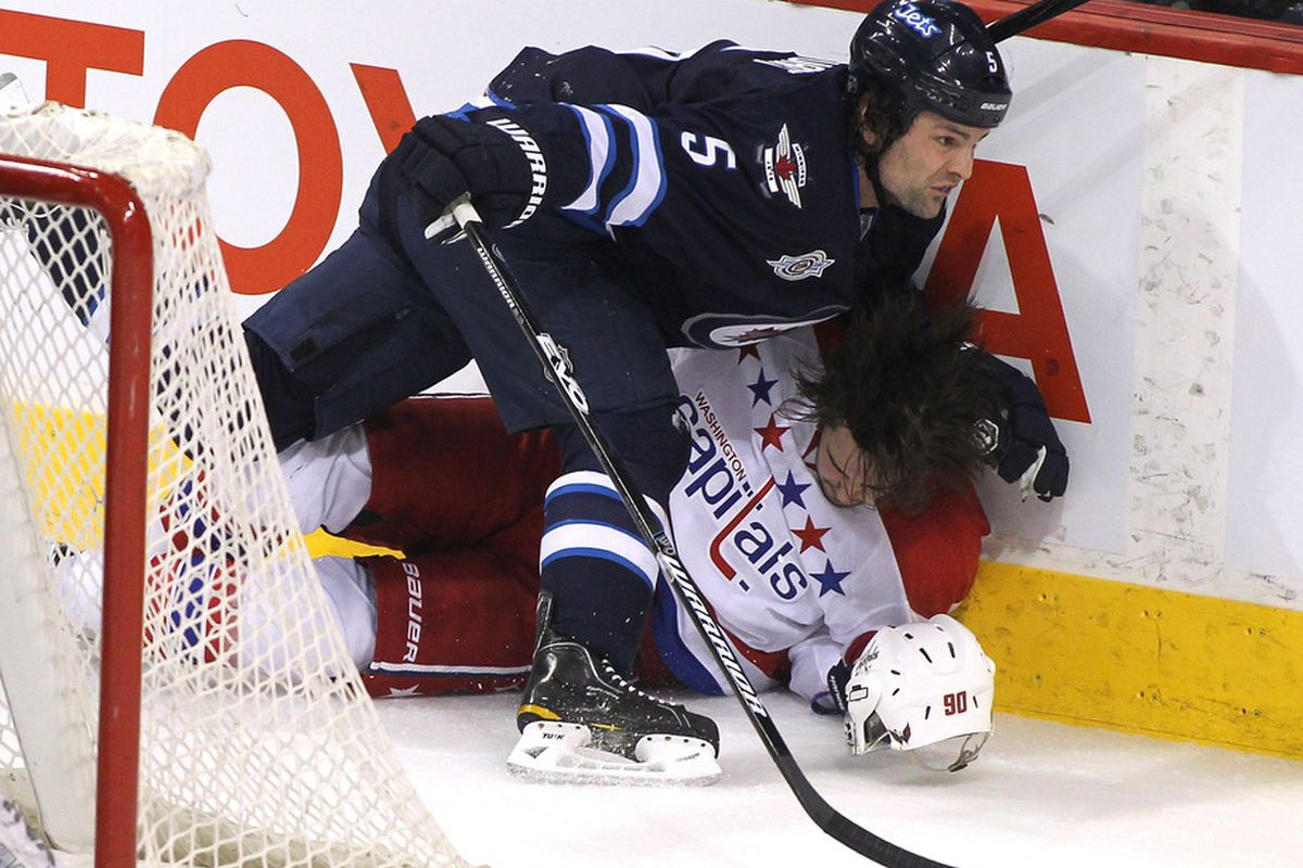 WINNIPEG, CANADA - MARCH 16: Mark Stuart #5 of the Winnipeg Jets collides with Marcus Johansson #90 of the Washington Capitals in NHL action at the MTS Centre on March 16, 2012 in Winnipeg, Manitoba, Canada. (Photo by Marianne Helm/Getty Images)