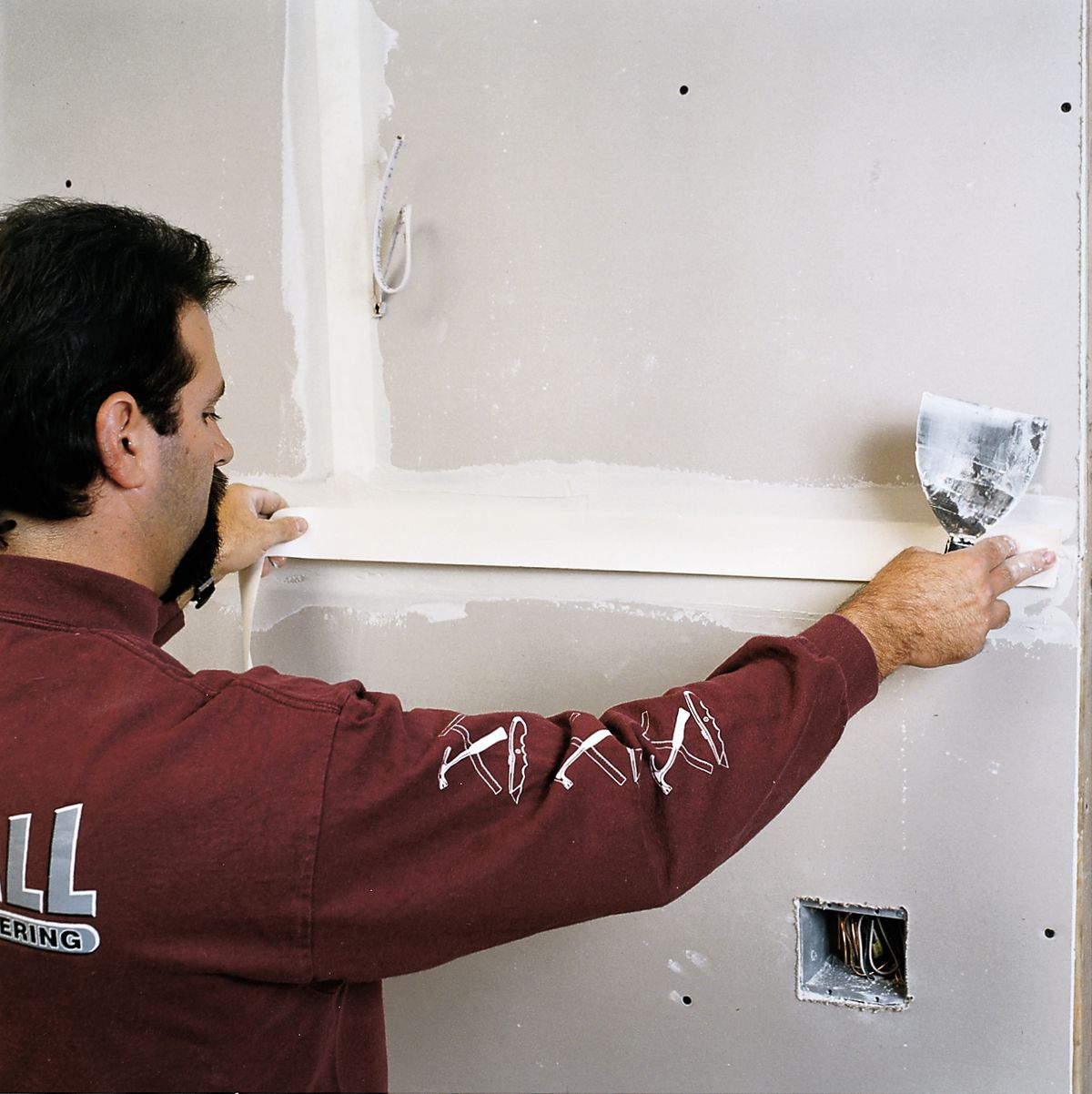 Man Applies Paper Tape To Drywall
